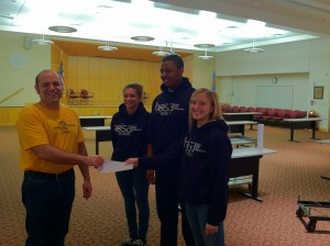 Paul Daigle accepts check presented by HOSA State Officers